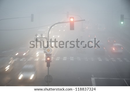 Road intersection in thick fog - blurred motion - stock photo