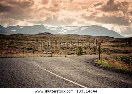 Road junction and waymarks at North Iceland mountain landscape. Filtered Image - stock photo