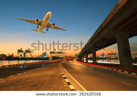 road ,land bridge run into ship port and commercial cargo plane flying above use for land ,air and vessel transport industry business - stock photo