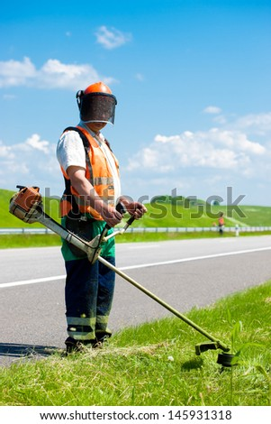 Road landscapers cutting grass along the road using string lawn trimmers - stock photo