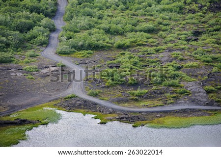 Road, lava field covered with green trees and lake near Myvatn lake in North Iceland, view from above - stock photo