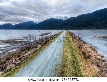 Road leading eye to distant mountains - stock photo
