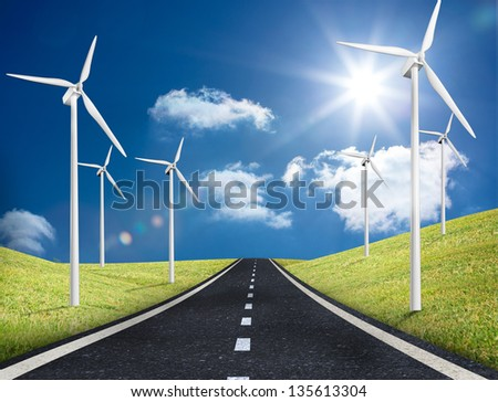 Road leading out to the horizon with wind turbines either side in the middle of a sunny field - stock photo