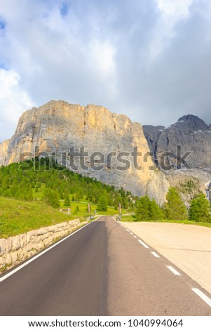 Road leading to high mountain ridge at Gardena pass or Passo Gardena in Dolomites, South Tyrol, Italy.