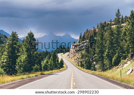 Road leading to mountains on a stormy day