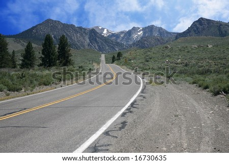 Road leading to snow spotted mountains with blue sky