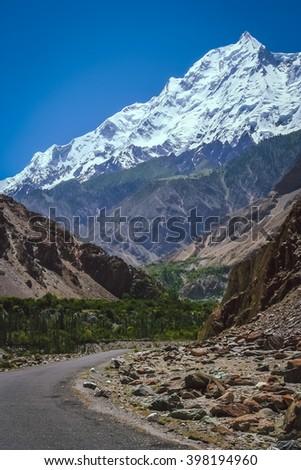 Road leading to the massive, imposing and beautiful Rakaposhi peak in Karakorum mountains, Pakistan - stock photo