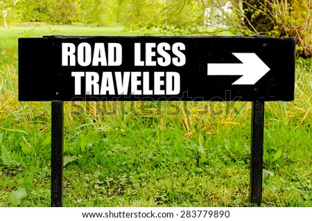 ROAD LESS TRAVELED written on directional black metal sign with arrow pointing to the right against natural green 