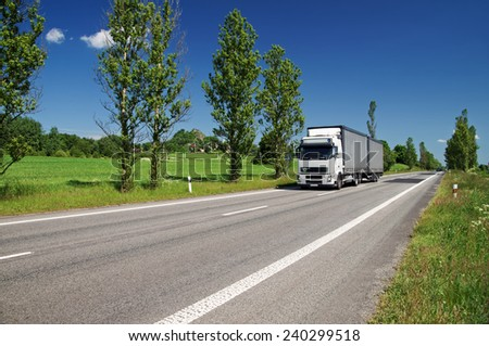 Road lined with poplar alley in the countryside, passing white truck, in the background of green fields, villages, mountain with the ruins of the castle - stock photo
