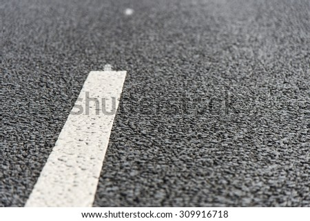 Road mark on the new asphalt. - stock photo
