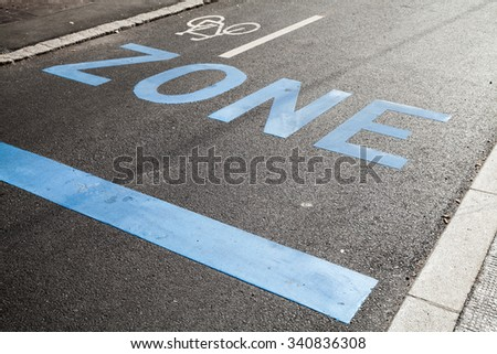 Road marking with blue text zone, stop line and bicycle sign