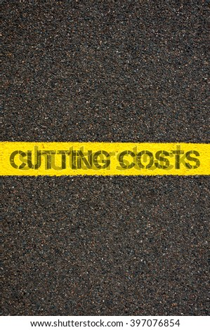 Road marking yellow paint dividing line with words CUTTING COSTS, concept image - stock photo