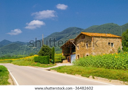 road near a traditional house in the Pyrenees. - stock photo