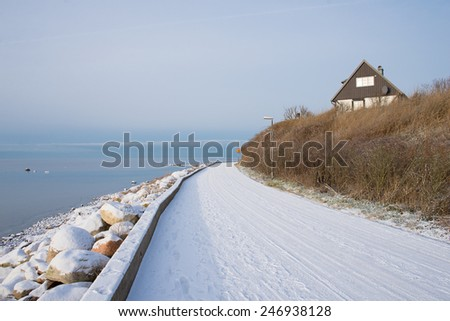 Road near the sea in winter in Sweden - stock photo