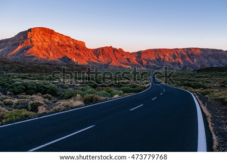Road on El Teide, the tall volcano on Tenerife island, with a classical vanishing point and the beautiful sunset warm light on the rocky mountains