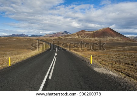 Road on Mars/Unusual landscape of a road going through a reddish volcanic region with rocks, hills and dust in vivid warm colors.