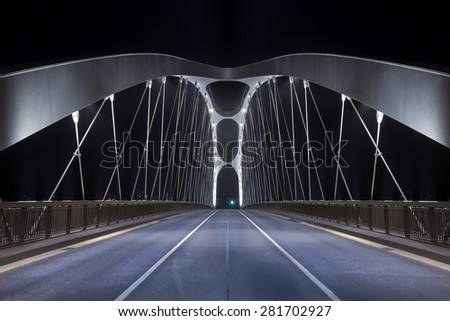 Road on modern frame bridge illuminated at night