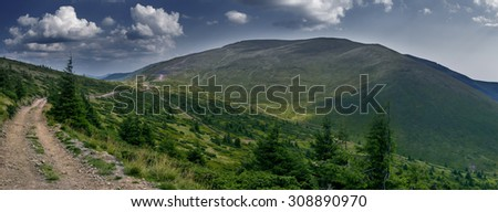 road on mountain slopes sky with clouds green grass carpathians europe