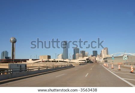 Road over a bridge leading into the city of Dallas, view of skyline - stock photo