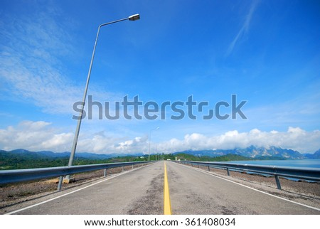 road over dam with blue sky background