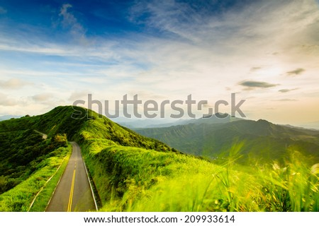 road passing the mountain by the sunset