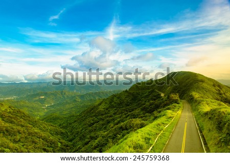 road passing the mountain by the sunset - stock photo