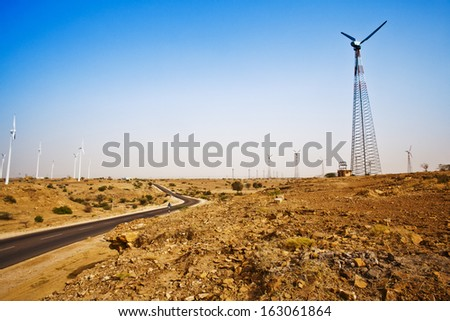Road passing through a desert with wind turbines in distance, Jaisalmer, Rajasthan, India - stock photo