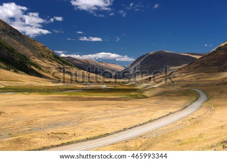 Road path on a desert wild mountain valley with the orange yellow dry grass at the background of the hills under a blue sky with white clouds, Plateau Ukok, Altai, Siberia, Russia