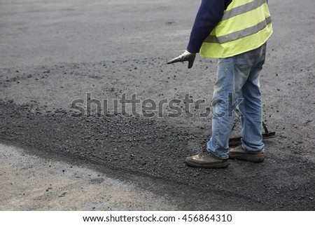 Road Paving Construction. Workers laying stone mastic asphalt during street repairing works. Worker making asphalt with coated chippings. Drainage repair, installation of manhole - stock photo