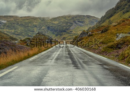 Road perspective in overcast weather. Norway landscape. - stock photo