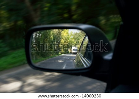 Road reflecting in the sideview mirror of a car - stock photo