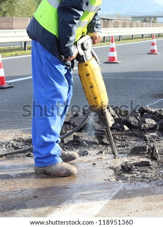 Road repairing works with jackhammer - stock photo