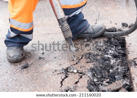 Road repairing works with jackhammer close up - stock photo