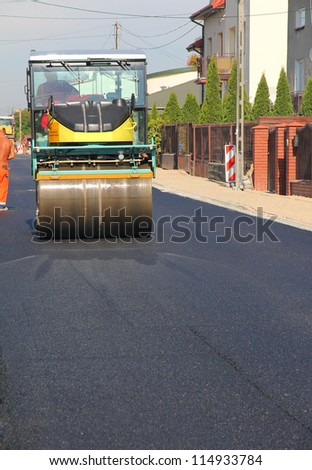 Road roller at a road - stock photo