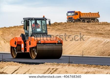 Road roller building the new asphalt road - stock photo
