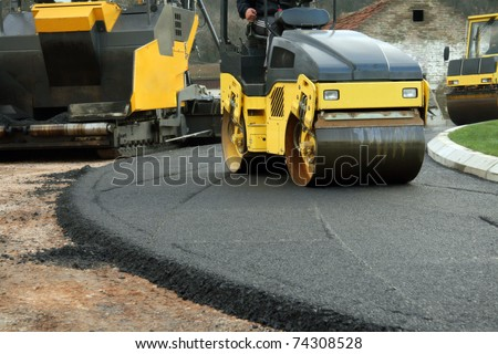Road roller machine works on the fresh asphalt