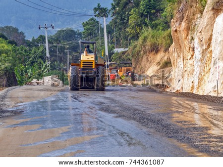 Road roller vibration machine compacting gravel base for asphalt pavement during construction roadworks, site of a new highway in jungle rainforest