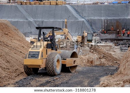 Road roller working in factory construction site foundation. - stock photo