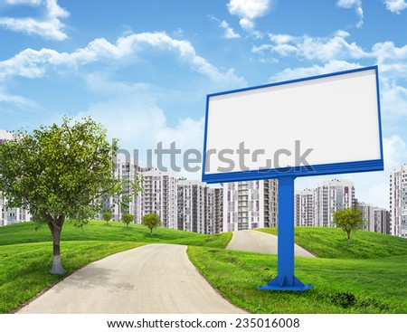 Road running through green hills leading toward city, Blank billboard and tree on foreground. High-rise buildings as backdrop - stock photo
