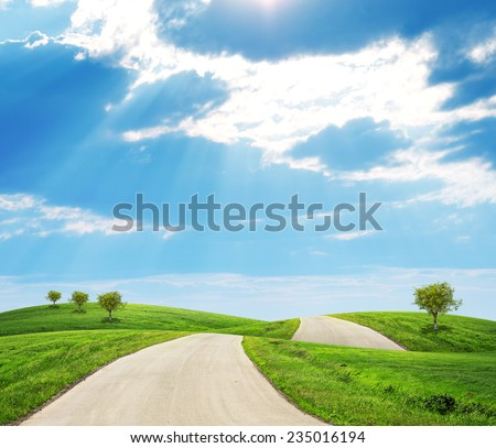Road running through green hills with a few trees - stock photo