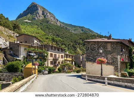 Road, rural houses and mountain on background under blue sky in small town of Tende, France. - stock photo