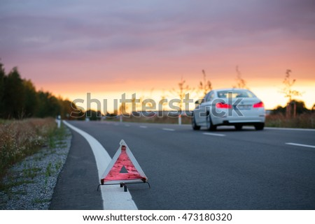 Road safety: emergency road triangle at the side of the road at sunset