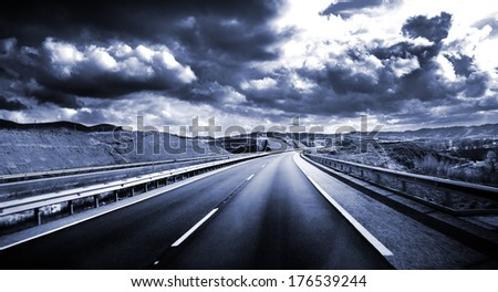 Road scenery. Travel concept.Cloudy sky and high road in blue toned  - stock photo