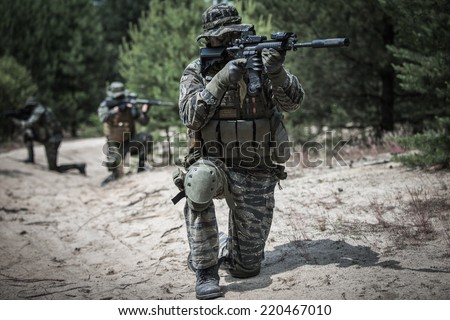 Road secured by special forces in tiger stripe camouflage - stock photo
