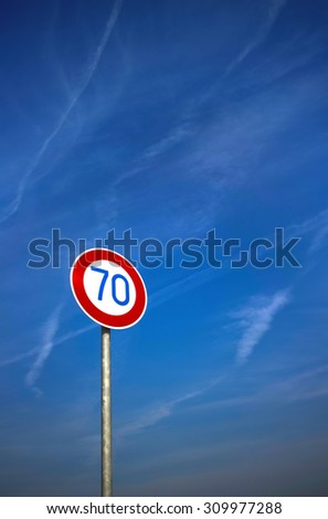 Road sign against blue sky with contrails