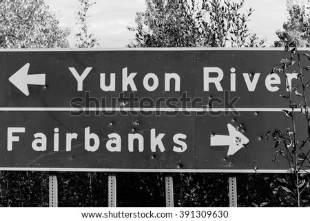 road sign along the Alaska Highway with direction to Yukon River or Fairbanks - stock photo