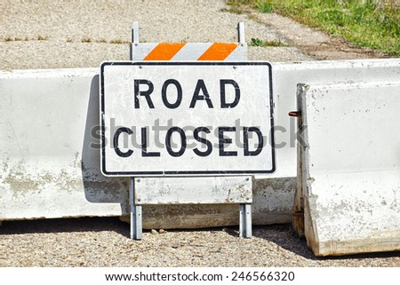 Road sign and concrete barriers are used to show road is closed.  - stock photo
