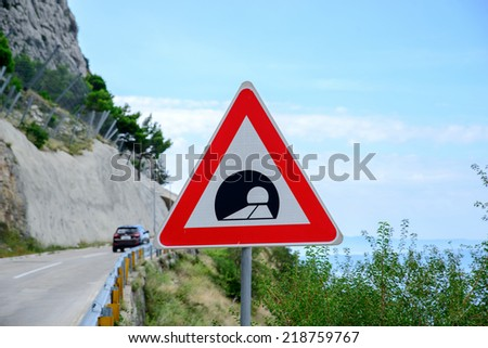 road sign announcing a tunnel in the mountains