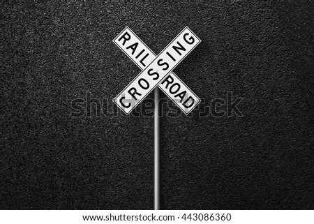 Road sign. Behind the sign one can see a smooth asphalt road. RAIL ROAD CROSSING. The texture of the tarmac, top view. - stock photo
