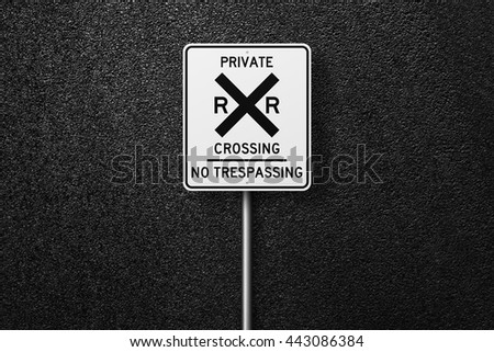 Road sign. Behind the sign one can see a smooth asphalt road. Railroad. Railway. The texture of the tarmac, top view. - stock photo
